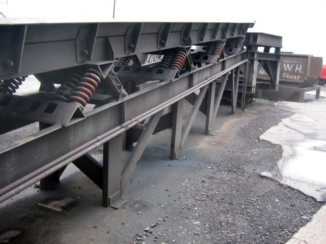 Conveyor system moving rebar into portable container