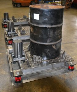 air powered vibrating tables settle sludge solids in 55 gallon drums