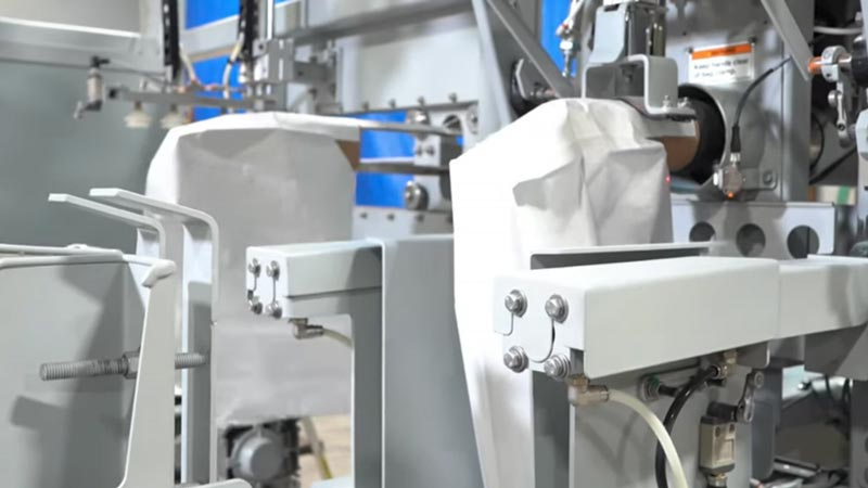 automatic bag placer placing empty bag on filling spout
