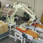palletizing robot picks bag up from conveyor and stacks it on pallet