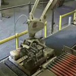 palletizing robot stacking filled bags of cement on pallet