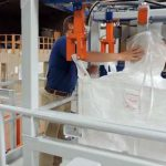 placing bulk bag spout around inflatable bag seal cuff and pre-fill bag inflator