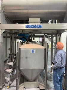 Blended seasoning mix being loaded into stainless steel IBC