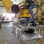 fanuc robot with tool picking up 40 pound bag of livestock feed