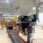 view of entire bagging system including gross weight bagging scale, conveyors, bag flattener, and palletizing robot