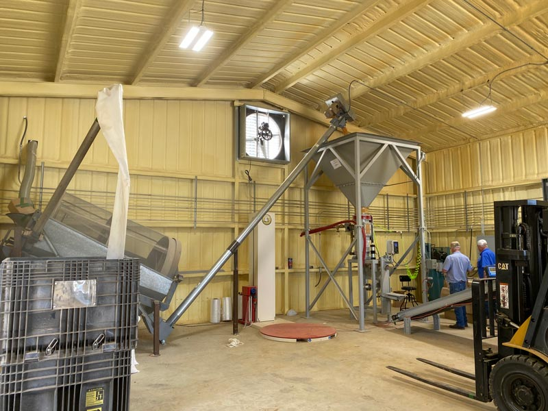 auger conveyor lifts corn into surge hopper above bagging machine