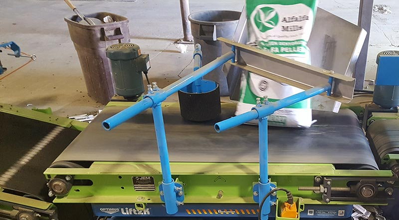 bag turner conveyor knocks down bags of alfalfa pellets