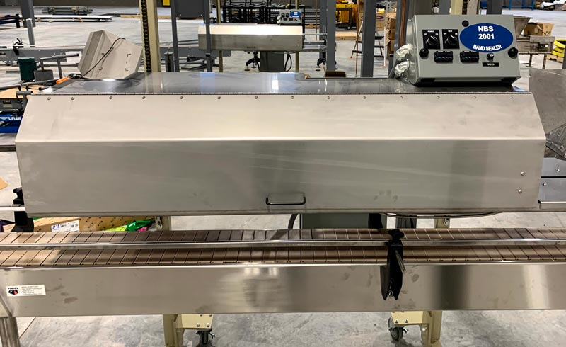 conveyor for stand up pouches or 5 lb bags with band sealer and closing device
