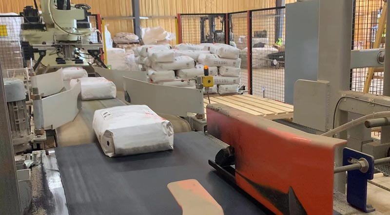 filled bags of aggregate on bag conveyor