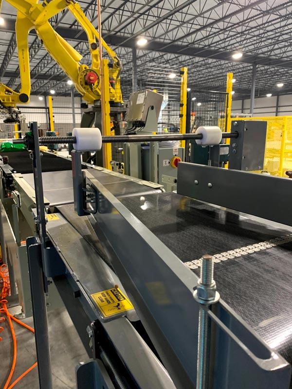 pacing conveyor to bag palletizing robot - jack screw can be adjusted to center bag on conveyor