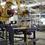 bag palletizing robot picks up bags of animal feed off of pick conveyor