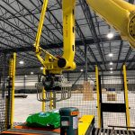 fanuc arm and tool picks up bags of dog food and palletizes them in automatic system