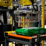 fanuc arm and tool picks bags of dog food and palletizes them in automatic system