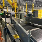 pacing conveyor to bag palletizing robot - jack screw can be adjusted to center bags on conveyor