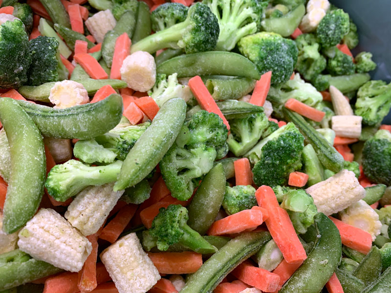 evenly coating frozen vegetables with topical seasoning using electrostatics